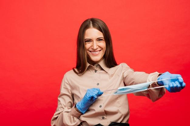 Rozochocona i radosna młoda kobieta bawić się z ochronną medyczną maską i błękitnymi rękawiczkami na czerwonym tle. portret z bliska. koniec kwarantanny koronawirusa, izolacja. covid-2019