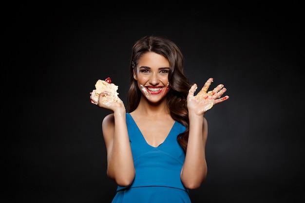 Rozochocona kobieta je kawałek tort w błękit sukni