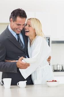 Rozochocona kobieta obejmuje dobrze ubierającego mężczyzna w kuchni