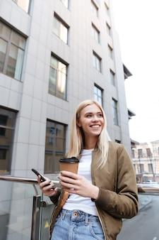 Rozochocona kobieta patrzeje na boku z filiżanką kawy i smartphone