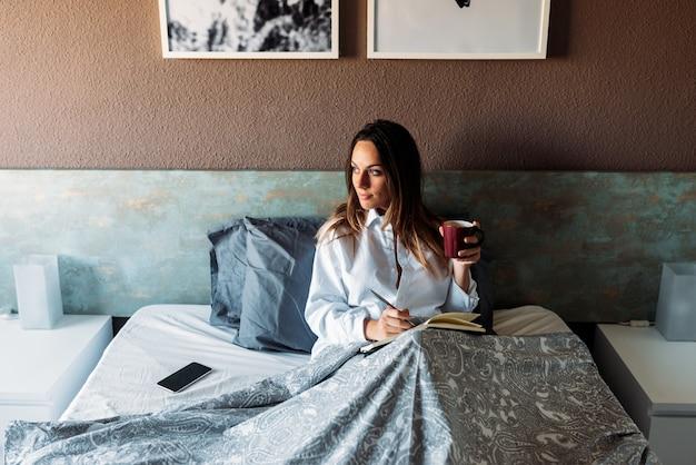 Rozochocona kobieta pije na łóżku z notatnikiem i piórem