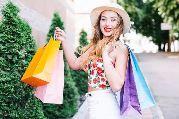 Rozochocona kobieta pokazuje papierowe torby przy kamerą