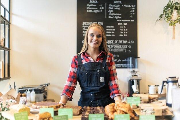 Rozochocona kobieta pracuje jako kelnerka w kawiarni