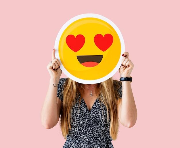 Rozochocona kobieta trzyma emoticon ikonę