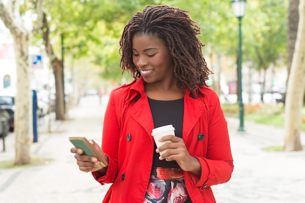 Rozochocona kobieta używa smartphone w parku