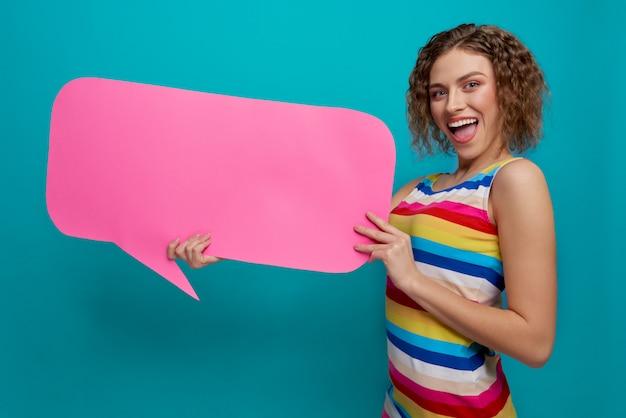 Rozochocona kobieta w sukni utrzymuje różową bąbel chmurę