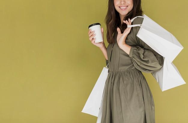 Rozochocona kobieta w sukni z kawą i zakupy zarabia netto