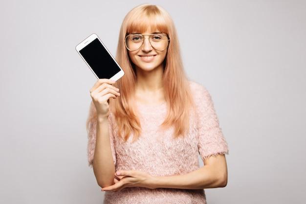 Rozochocona kobieta w szkłach pokazuje smartphone ekran, patrzeje kamerę