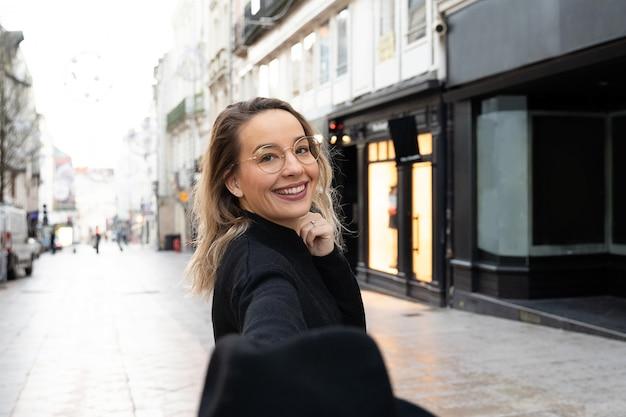 Rozochocona kobieta z białym uśmiechu odprowadzeniem na europejskim ulicznym zwiedzać.