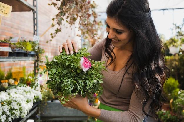 Rozochocona kobieta z doniczkowym kwiatem