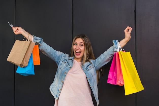 Rozochocona kobiety pozycja z kolorowymi torba na zakupy
