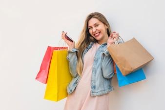 Rozochocona kobiety pozycja z smartphone i torba na zakupy
