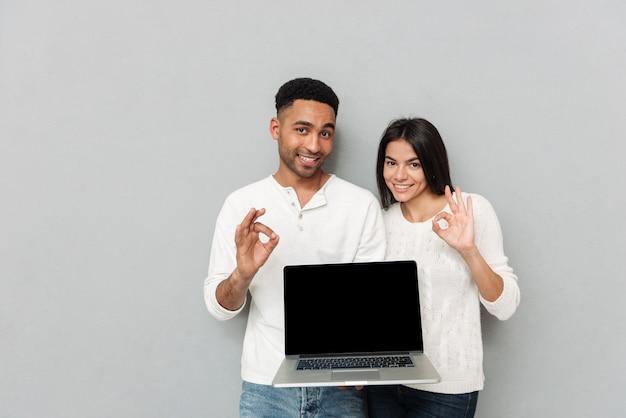 Rozochocona kochająca para pokazuje pokazu laptop