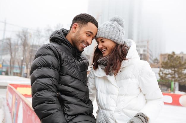 Rozochocona kochająca pary łyżwiarstwo przy lodowym lodowiskiem outdoors.