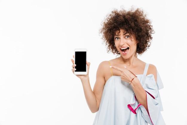Rozochocona ładna kobieta wskazuje palec przy pustego ekranu telefonem komórkowym