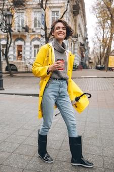 Rozochocona ładna młoda kobieta ubierająca w gumowych butach