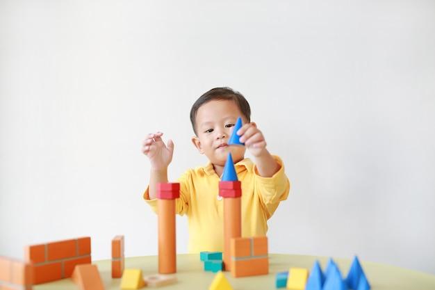 Rozochocona mała chłopiec bawić się kolorową drewnianego bloku zabawkę na stole.