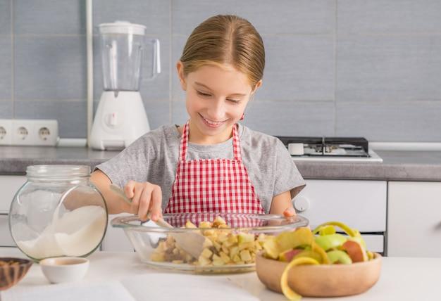 Rozochocona mała dziewczynka miesza składniki dla strudla plombowania