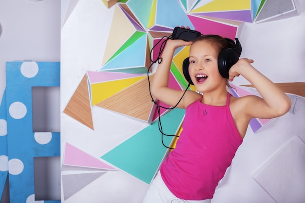 Rozochocona mała dziewczynka słucha muzyka i śpiewa z hełmofonami