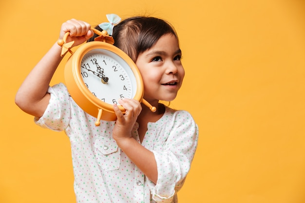Rozochocona mała dziewczynka trzyma zegarowego alarm.