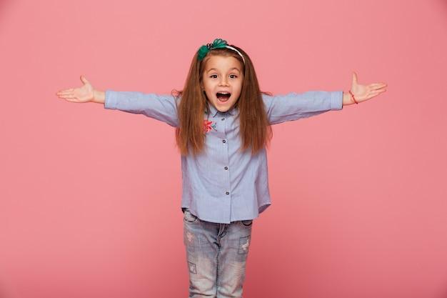 Rozochocona mała dziewczynka w włosianym obręczu pozuje z otwartymi rękami jest przyjazny i gościnny