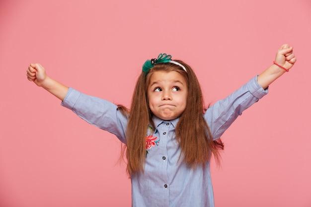 Rozochocona mała dziewczynka w włosianym obręczu z zaciśniętymi wargami stawia zaciśnięte pięści rękami w powietrzu