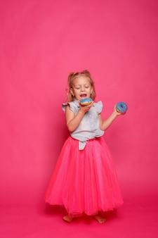 Rozochocona mała dziewczynka z pączkiem. dziecko oddaje się jedzeniu. zabawa z pączkami