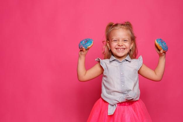 Rozochocona mała dziewczynka z pączkiem na różowym tle. dziecko rozkoszuje się jedzeniem. zabawa z pączkami