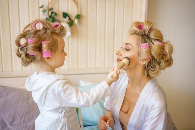 Rozochocona mama i córka na łóżku robi makijażowi