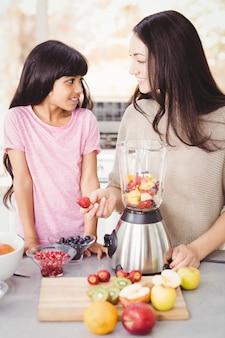 Rozochocona matka i córka przygotowywa sok owocowego