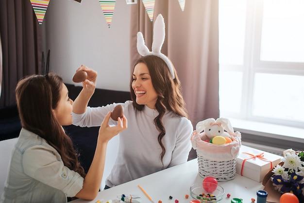 Rozochocona matka i córka przygotowywamy na wielkanoc. trzymają czekoladowe jajka i uśmiechają się. dekoracja na stole. model nosić białe uszy królika.