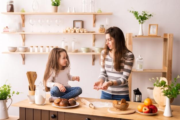 Rozochocona matka i córka w kuchennym narządzania śniadaniu. zagnieść ciasto z mąki na naleśniki, ciastka i bułki.