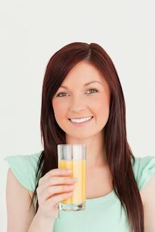 Rozochocona miedzianowłosa kobieta cieszy się szkło sok pomarańczowy w kuchni