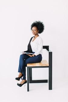 Rozochocona młoda afro amerykańska biznesowa kobieta opowiada na telefonie komórkowym, siedzi na krześle, odizolowywającym na bielu
