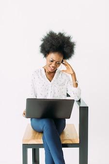 Rozochocona młoda afro amerykańska biznesowa kobieta skoncentrowana i zmieszana, używać laptop, odizolowywającego na bielu