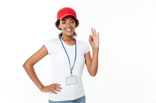 Rozochocona młoda afrykańska dama jest ubranym nakrętkę pokazuje zadowalającego gest.