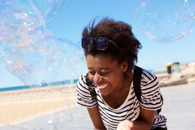 Rozochocona młoda afrykańska kobieta bawić się z mydlanym bąblem outdoors przy plażą