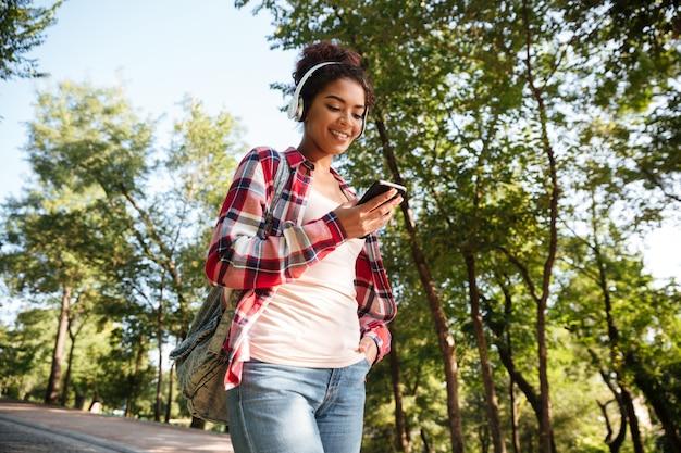 Rozochocona młoda afrykańska kobieta chodzi outdoors