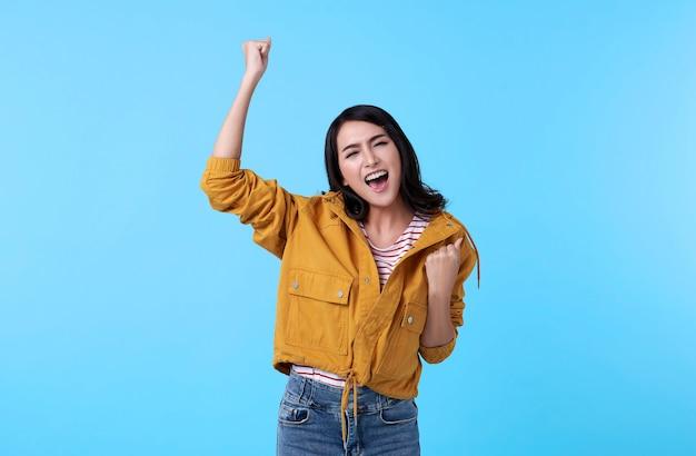 Rozochocona młoda azjatycka kobieta podnosi jego pięści z uśmiechniętą zadowoloną twarzą, tak gest, świętuje sukces na błękitnym tle.