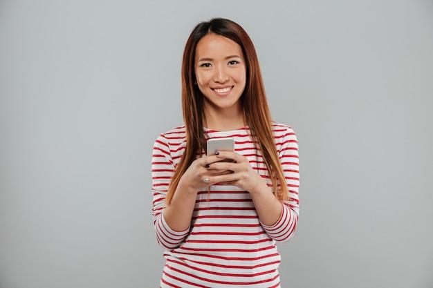 Rozochocona młoda azjatykcia kobieta gawędzi telefonem