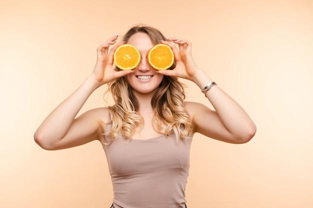 Rozochocona młoda blondynka pozuje z świeżymi pomarańczami