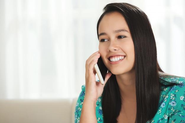 Rozochocona młoda brunetka opowiada na smartphone w domu