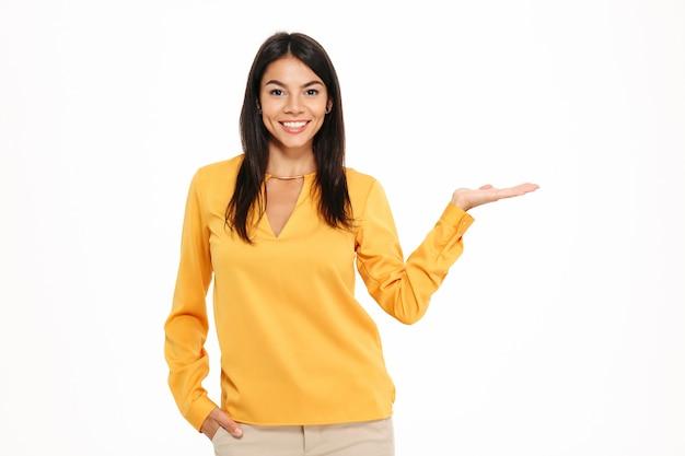 Rozochocona młoda dama w żółtej koszulowej mienia copyspace w ręce.