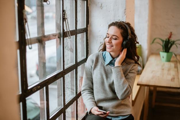 Rozochocona młoda dziewczyna słucha muzyka z hełmofonem blisko okno.