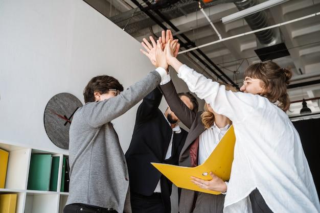 Rozochocona młoda grupa ludzi stoi w biurze i daje piątce