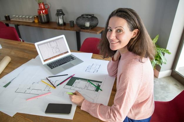 Rozochocona młoda kobieta egzamininuje projekty w domu