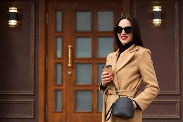 Rozochocona młoda kobieta jest ubranym beżowego żakiet, czarnego pulower, ma torebkę i okulary przeciwsłonecznych, pije kawę na wynos w papierowej filiżance, pozuje uśmiecha się przeciw budynkowi miasta, czeka partnera biznesowego na spotkanie.