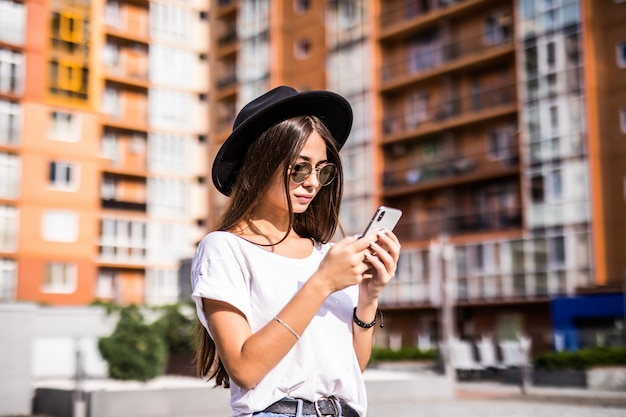 Rozochocona młoda kobieta jest ubranym czarnego kapelusz w miasto ulicie pisać na maszynie wiadomość.
