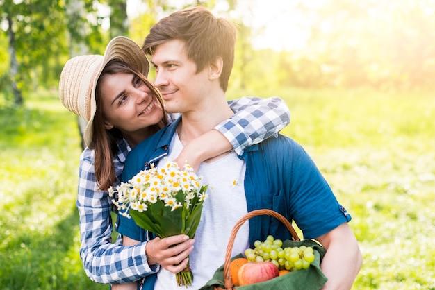 Rozochocona młoda kobieta obejmuje kochanka w parku