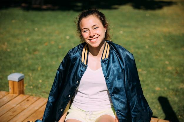 Rozochocona młoda kobieta odpoczywa przy sportsground